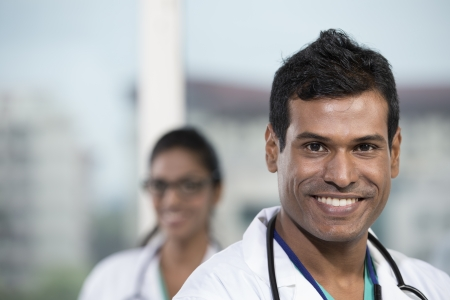 Portrait of a male Indian doctor standing in front of his colleague with a stethoscope around his neck Stock Photo - 22240247