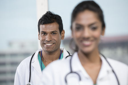south asian: Portrait of a female Indian doctor standing in front of her colleague with a stethoscope around her neck