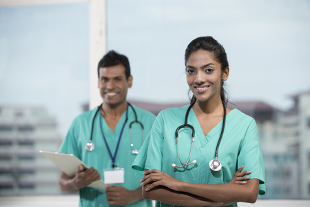 asian nurse: Portrait of a female Indian doctor standing in front of her colleague with a stethoscope around her neck