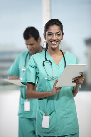 Portrait of a female Indian doctor standing in front of her colleague holding a digital tablet PC photo
