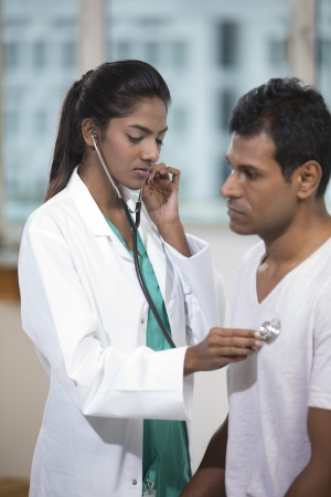 Female Indian doctor checking male patient's chest with a stereoscope. Stock Photo - 22240262