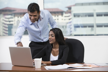 Indian business man and woman working together at a desk in an office photo