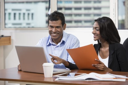 indian business man: Indian business man and woman working together at a desk in an office