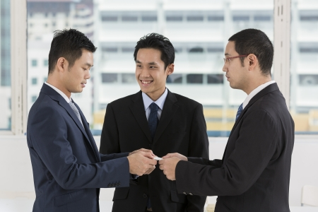 Two business men exchanging business cards. Caucasian and asian business men swapping business cards photo