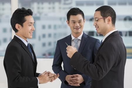 Deux hommes d'affaires d'échanger des cartes d'affaires. Les hommes d'affaires du Caucase et d'Asie échanger des cartes de visite