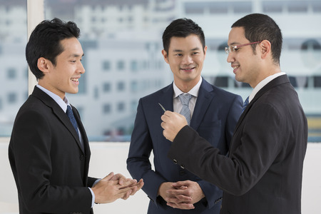 businessmen shaking hands: Two business men exchanging business cards. Caucasian and asian business men swapping business cards Stock Photo