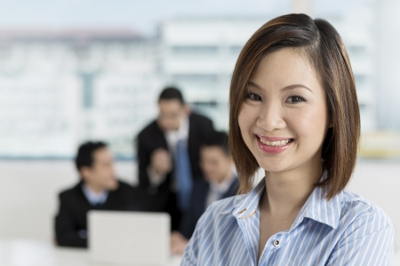caucasians: A group of business people lead by a happy Chinese Businesswoman.