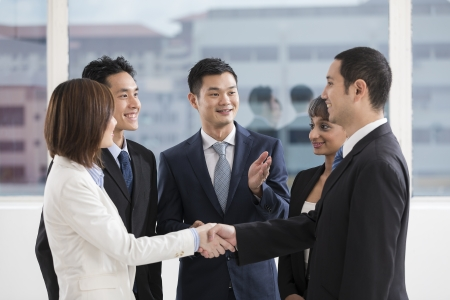 asian executive: business people shaking hands with a team of colleagues around them