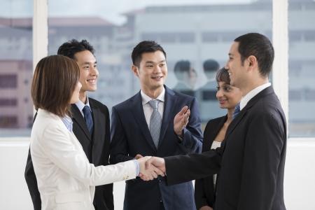 les gens d'affaires se serrant la main avec une équipe de collègues autour d'eux