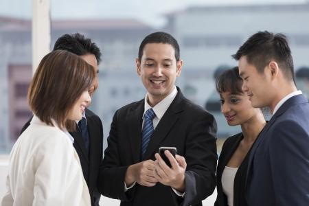 スマート フォンで探しているビジネス人々 の多民族グループ