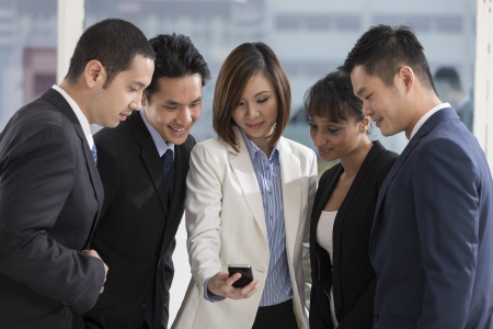 A multi ethnic group of business people looking at a smartphone Stock Photo