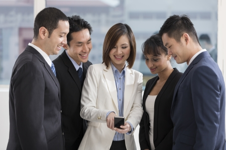 Un groupe multi-ethnique des gens d'affaires à la recherche d'un smartphone Banque d'images