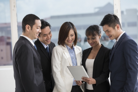 A group of muliethnic Business people using a digital tablet in the office. Stock Photo