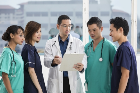 Group of doctors and nurses standing in a hospital. Multi-ethnic team of caucasian, Chinese and indian medical staff. Stock Photo