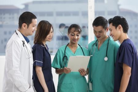 Groupe de médecins et d'infirmières debout dans un hôpital. Équipe multi-ethnique caucasienne, le personnel médical chinois et indien.