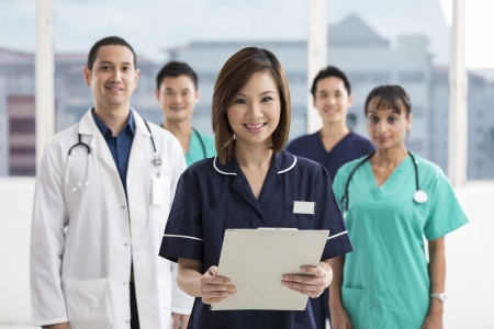 Nurses standing in a hospital with her team in background. Multi-ethnic team of caucasian, Chinese and indian medical staff. photo