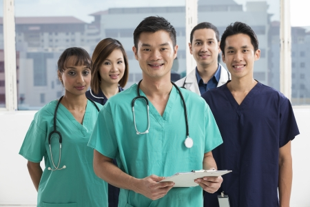 hospital staff: Group of doctors and nurses standing in a hospital. Multi-ethnic team of caucasian, Chinese and indian medical staff. Stock Photo