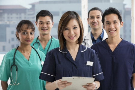 Nurses standing in a hospital with her team in background. Multi-ethnic team of caucasian, Chinese and indian medical staff.