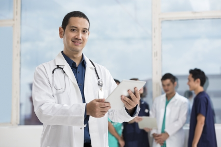 Mixed race Caucasian and pan-asian doctor using a digital tablet PC.