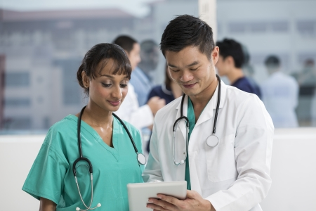 asian nurse: Team of mixed race doctors and medical staff using a digital tablet PC.