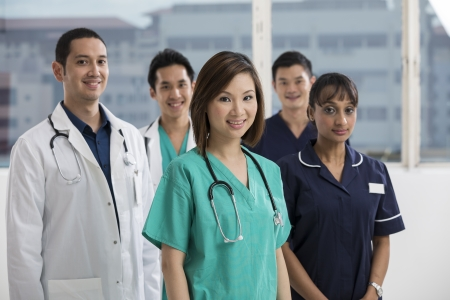 asian doctor: Group of doctors and nurses standing in a hospital. Multi-ethnic team of caucasian, Chinese and indian medical staff. Stock Photo