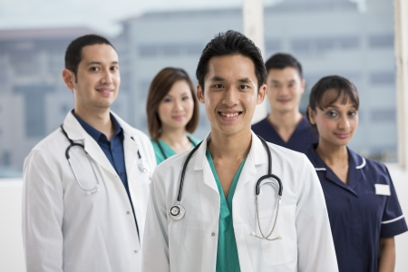 Group of doctors and nurses standing in a hospital. Multi-ethnic team of caucasian, Chinese and indian medical staff. photo