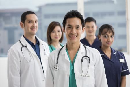 Groupe de médecins et d'infirmières debout dans un hôpital. Équipe multi-ethnique du Caucase, le personnel médical chinois et indien.