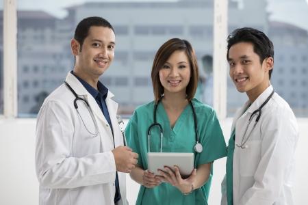 grupo de médicos: Equipo médico de raza mixta y el personal médico usando un Tablet PC digital. Foto de archivo
