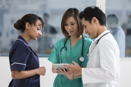 modern doctor: Team of mixed race doctors and medical staff using a digital tablet PC.