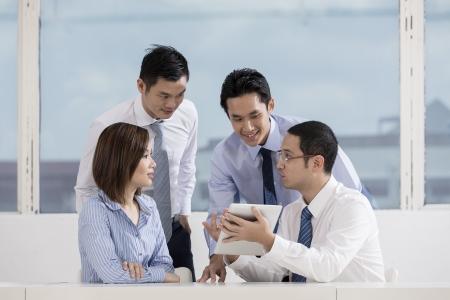 Un gruppo di uomini d'affari che lavorano insieme muliethnic. Utilizzando una tavoletta digitale in ufficio. Archivio Fotografico - 22365688