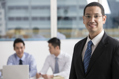 asian businessman: A group of business people lead by a happy caucasian Business man.