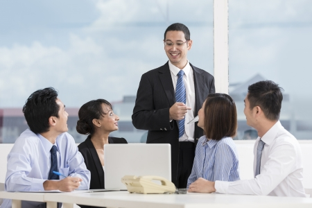leadership training: Multi-race business team working together around a laptop computer Stock Photo