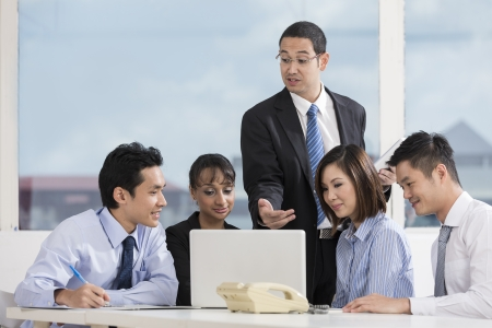 Multi-race business team working together around a laptop computer photo