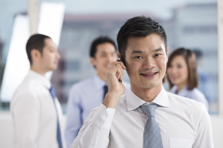 A Chinese business man making a phone call with his team in the background.   photo