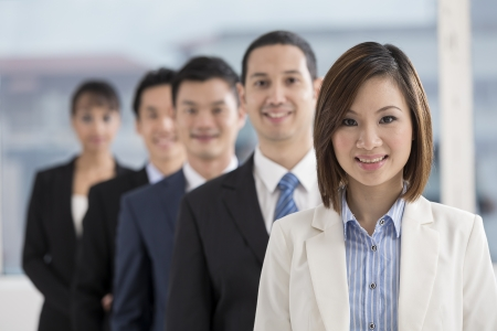 indian professional: A group of business people lead by a happy Chinese Businesswoman.