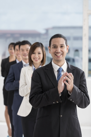 people clapping: A team of business people celebrating. Multi ethnic business team. Stock Photo