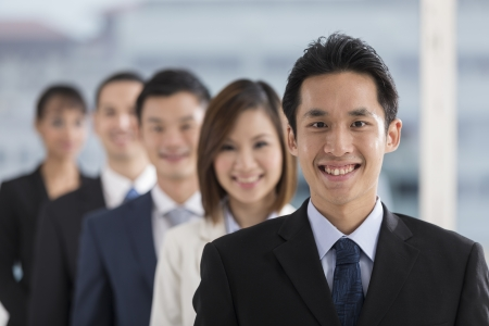 Un groupe de gens d'affaires dirigé par un homme d'affaires heureux chinois.