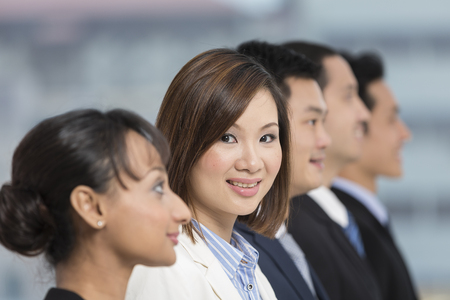 A group of business people lead by a happy Chinese Businesswoman. photo