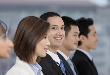 A group of business people lead by a happy caucasian Business man. photo