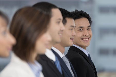 A group of business people lead by a happy Chinese Business man. photo