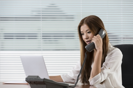 Young Asian woman at work in an office talking on the phone. photo