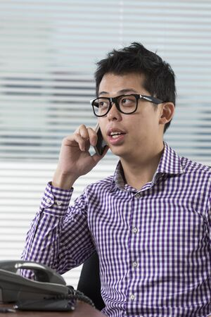 telephone salesman: Happy Chinese businessman talking on the phone in his office. Asian business executive at work. Stock Photo