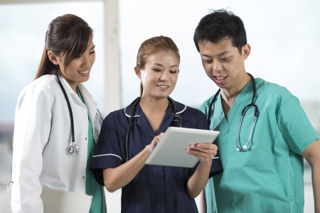 medical worker: Team of Asian doctors and nurses using a digital tablet PC. Stock Photo