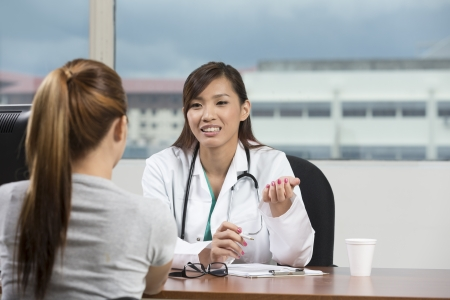Chinese doctor talking with female patient in doctors office.