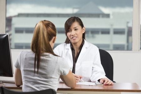 asian medical: Chinese doctor talking with female patient in doctors office.