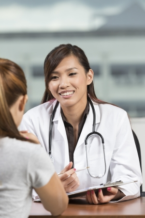 medical questions: Chinese doctor talking with female patient in doctors office.