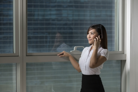 Beautiful Chinese business woman talking on a phone and looking out of the window photo
