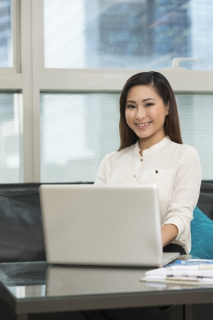 Young Chinese business woman working from home. Asian female using a laptop. photo