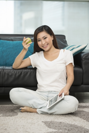 Young Chinese woman at home relaxing in her lounge reading a digital tablet PC. photo