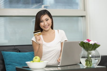 Young Chinese woman at home relaxing on Sofa and Shopping Online photo